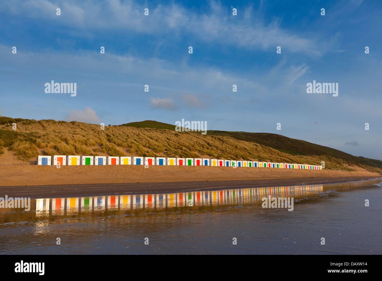 A long line of white beach huts, with coloured doors, stand in front of dunes with reflections in the wet beach - Stock Image
