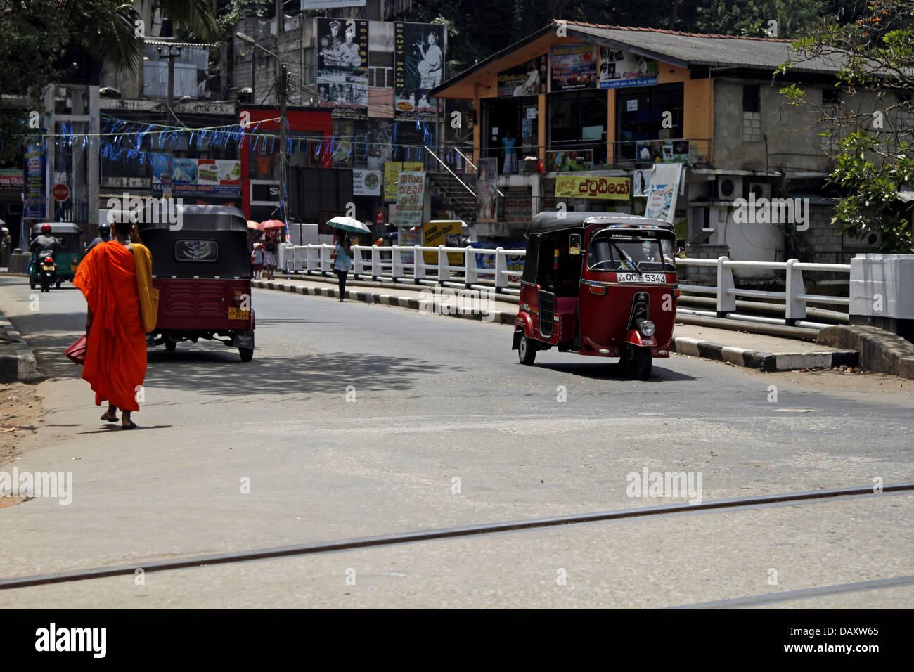 MONK IN ORANGE ROBE & TUC TUCS PERADENIYA SRI LANKA 12 March 2013 - Stock Image