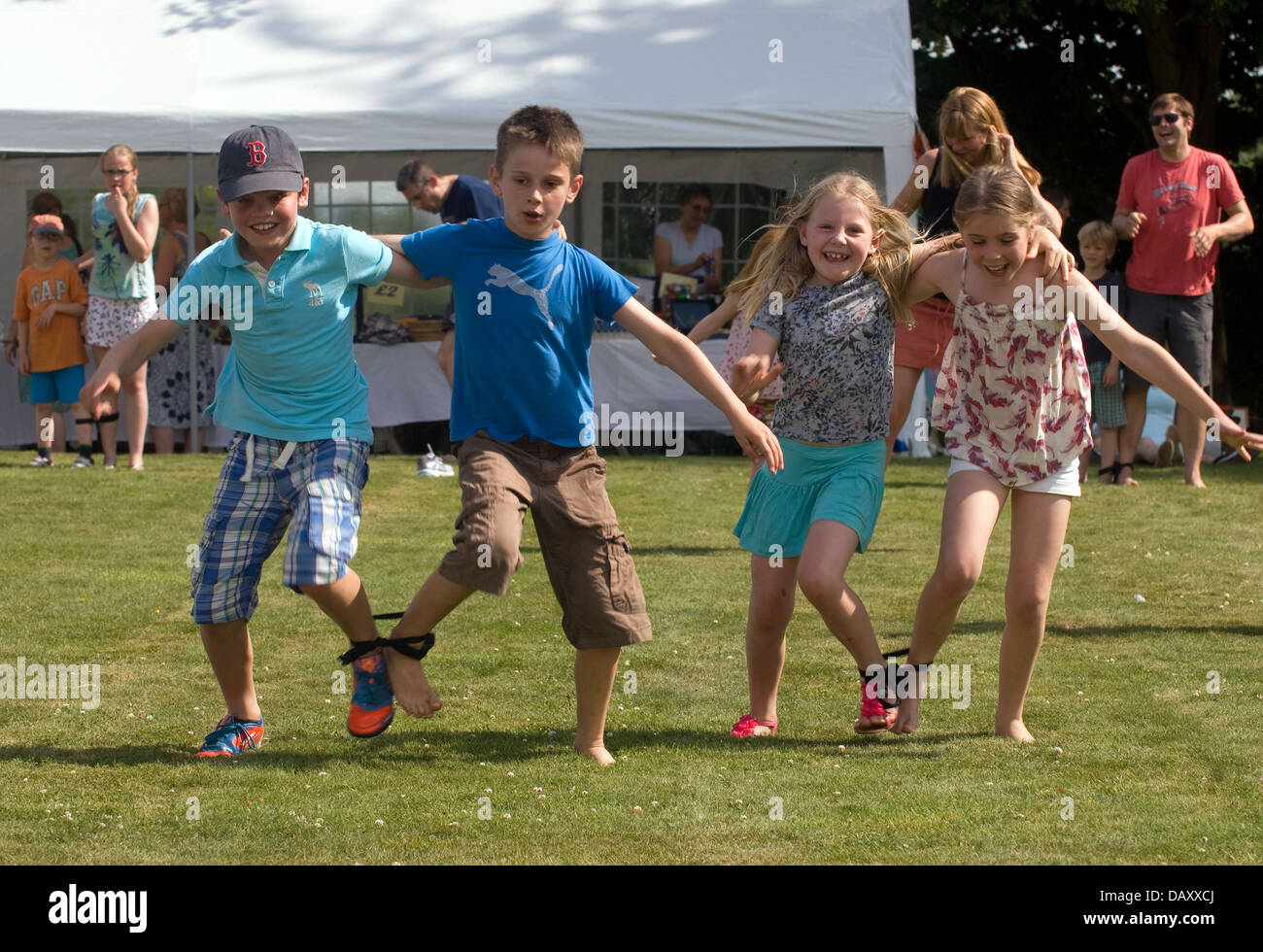 Youngsters taking part in a two-legged race at Worldham Village Fete, Hampshire, UK. Sunday 14 July 2013. - Stock Image