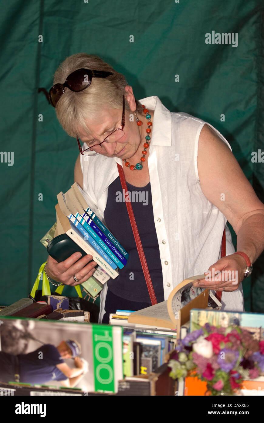 Woman browsing book stall at Worldham Village Fete, Hampshire, UK. Sunday 14 July 2013. - Stock Image