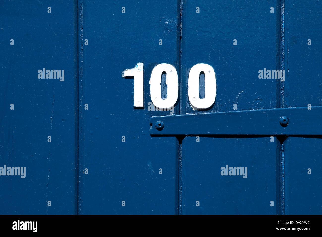number one hundred on blue gate - Stock Image