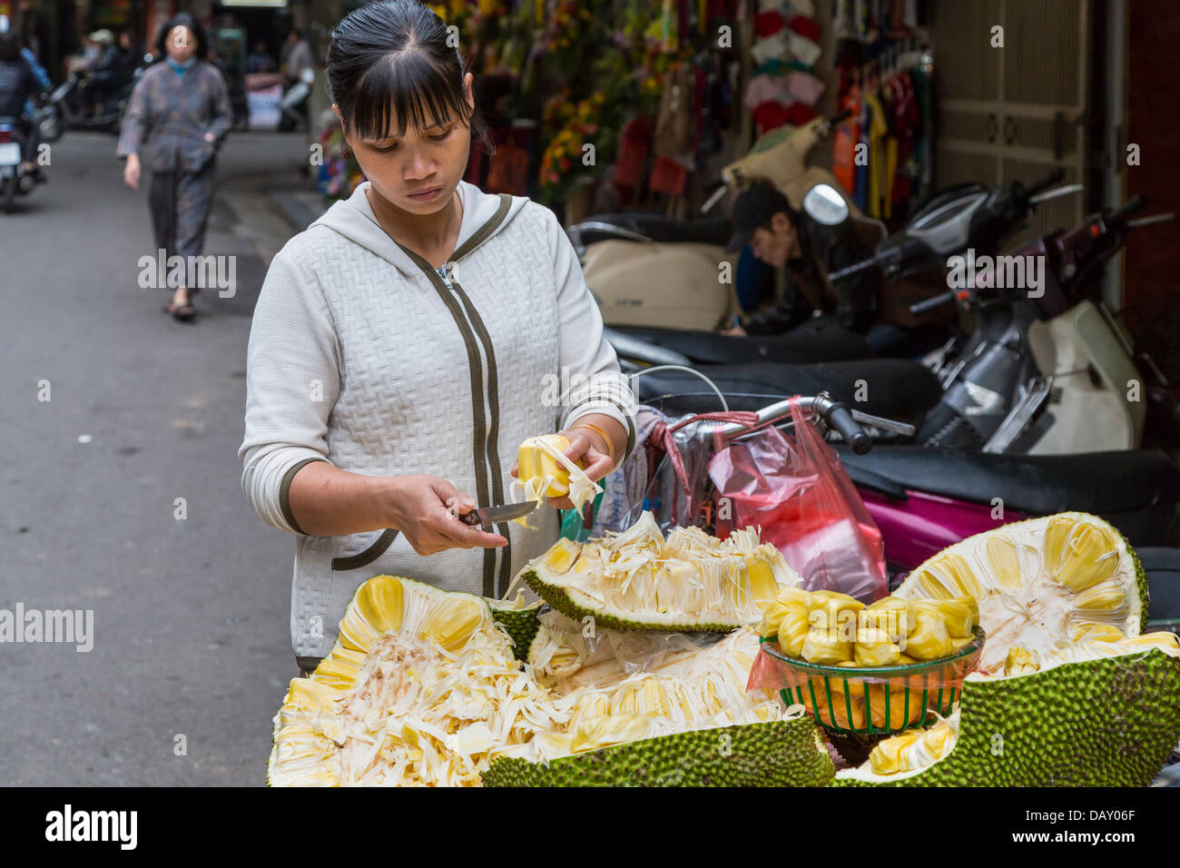 A young lady street vendor selling fresh fruit and pastry in Hanoi, Vietnam, Asia. - Stock Image