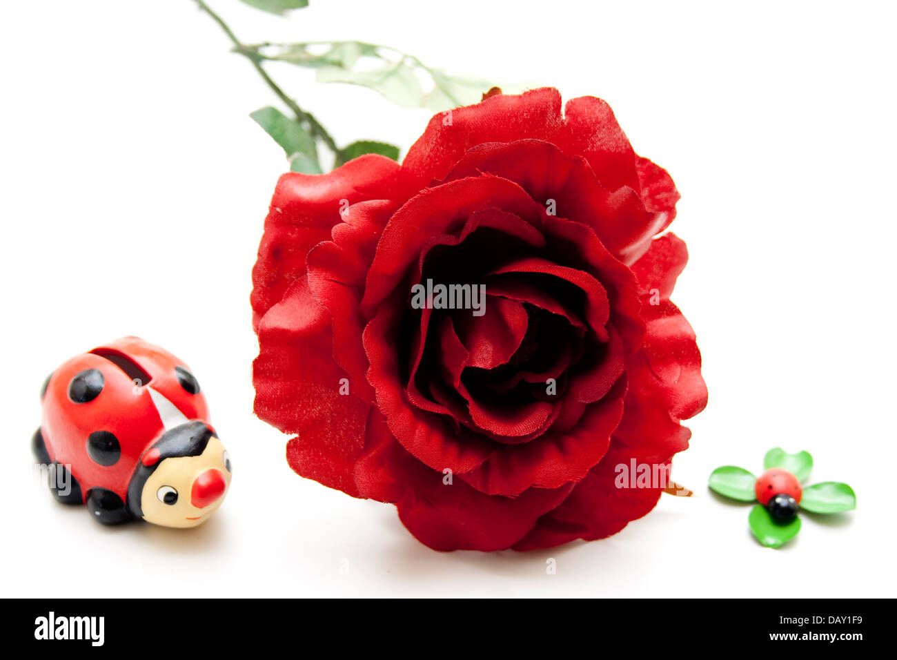 Red rose with ceramic beetle - Stock Image