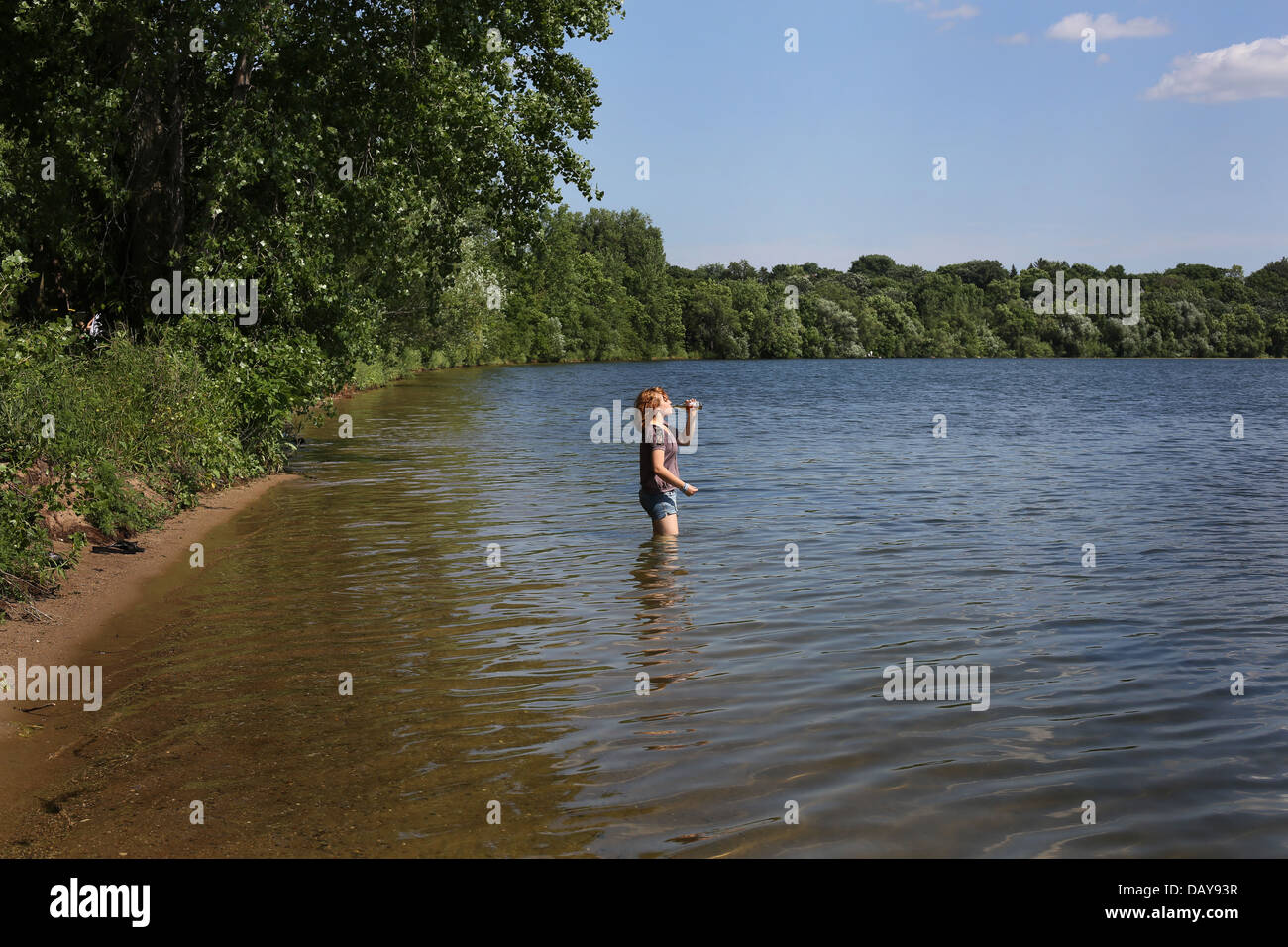 A teen girl standing in a lake and drinking a beverage from a bottle. - Stock Image