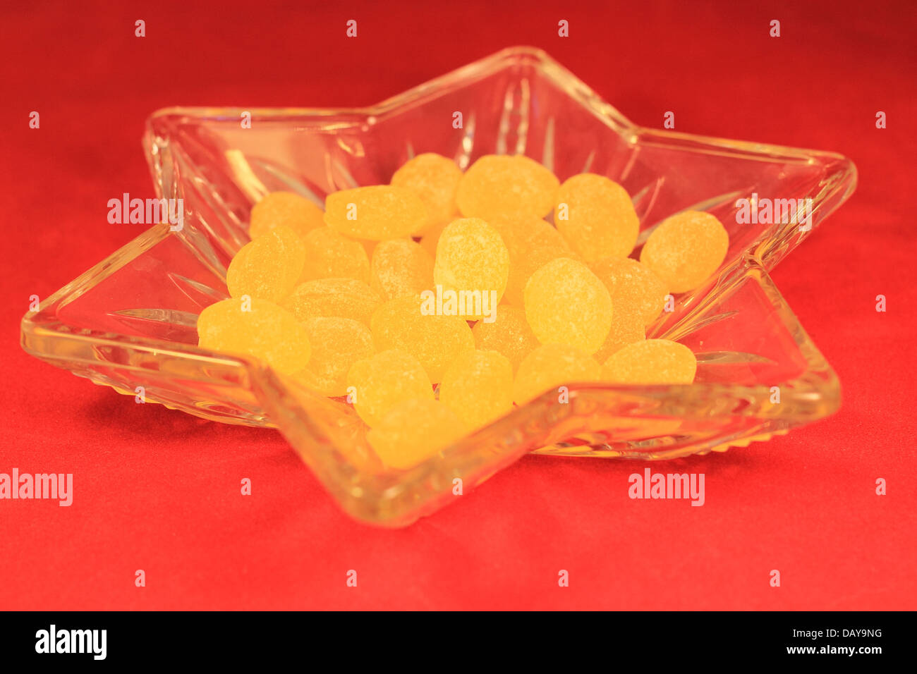 Lemon drops in a candy dish on a red background - Stock Image