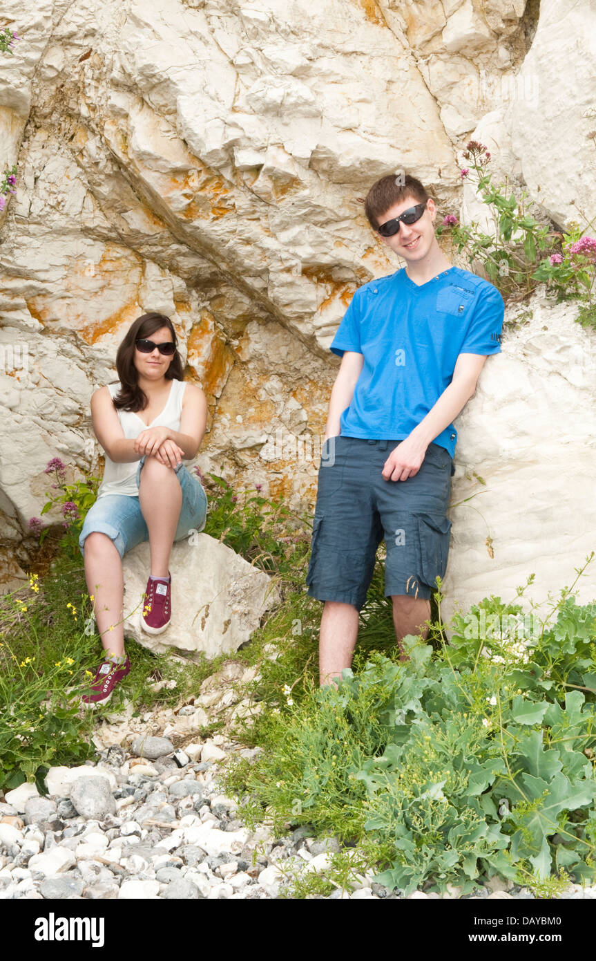 A young relaxed couple in their late teens or early twenties wearing casual clothing and sunglasses - Stock Image