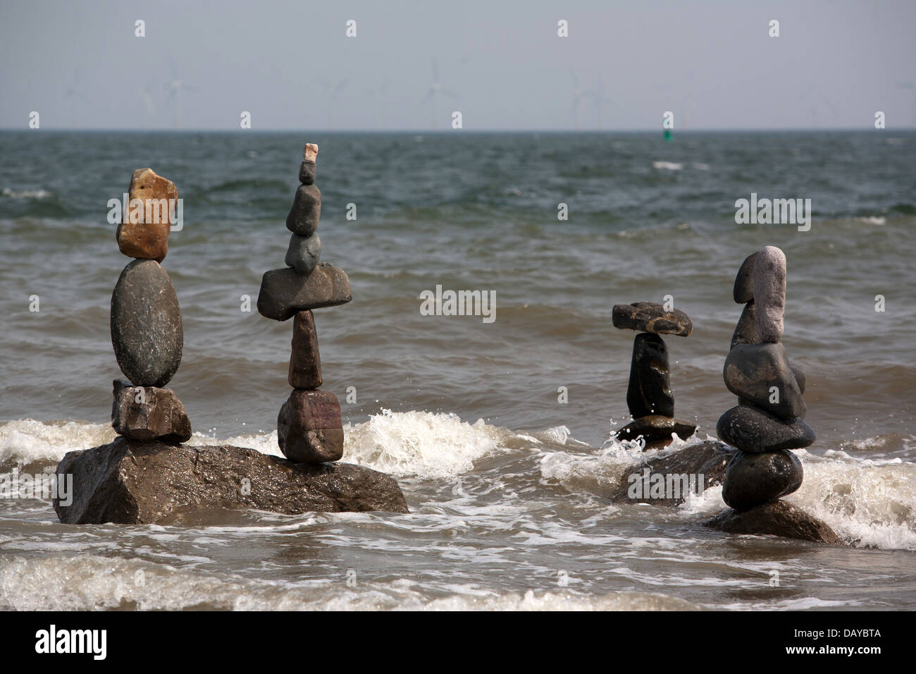 Carefully balanced stones stand as the tide rises on Rhos On Sea beach. Pic Colin Paxton/CP Photography - Stock Image