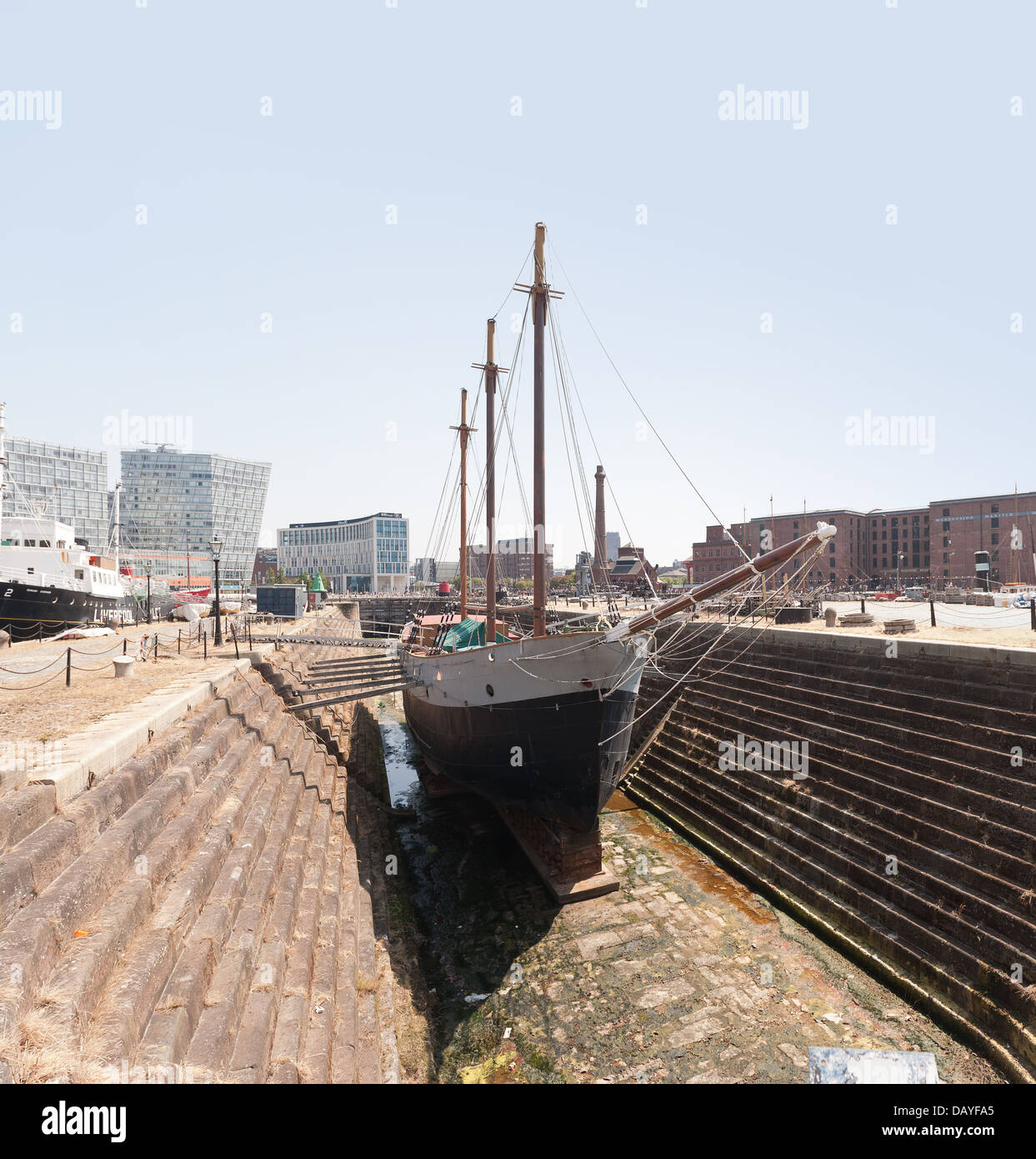 The De Wadden trading sailing ship boat in Canning dry dock against modern rebuild skyline contrasts older traditional - Stock Image
