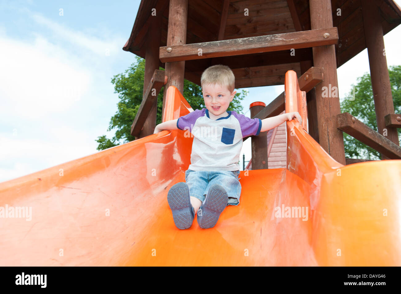 A cute smiling young child aged three sliding down an orange slide at a playground - Stock Image