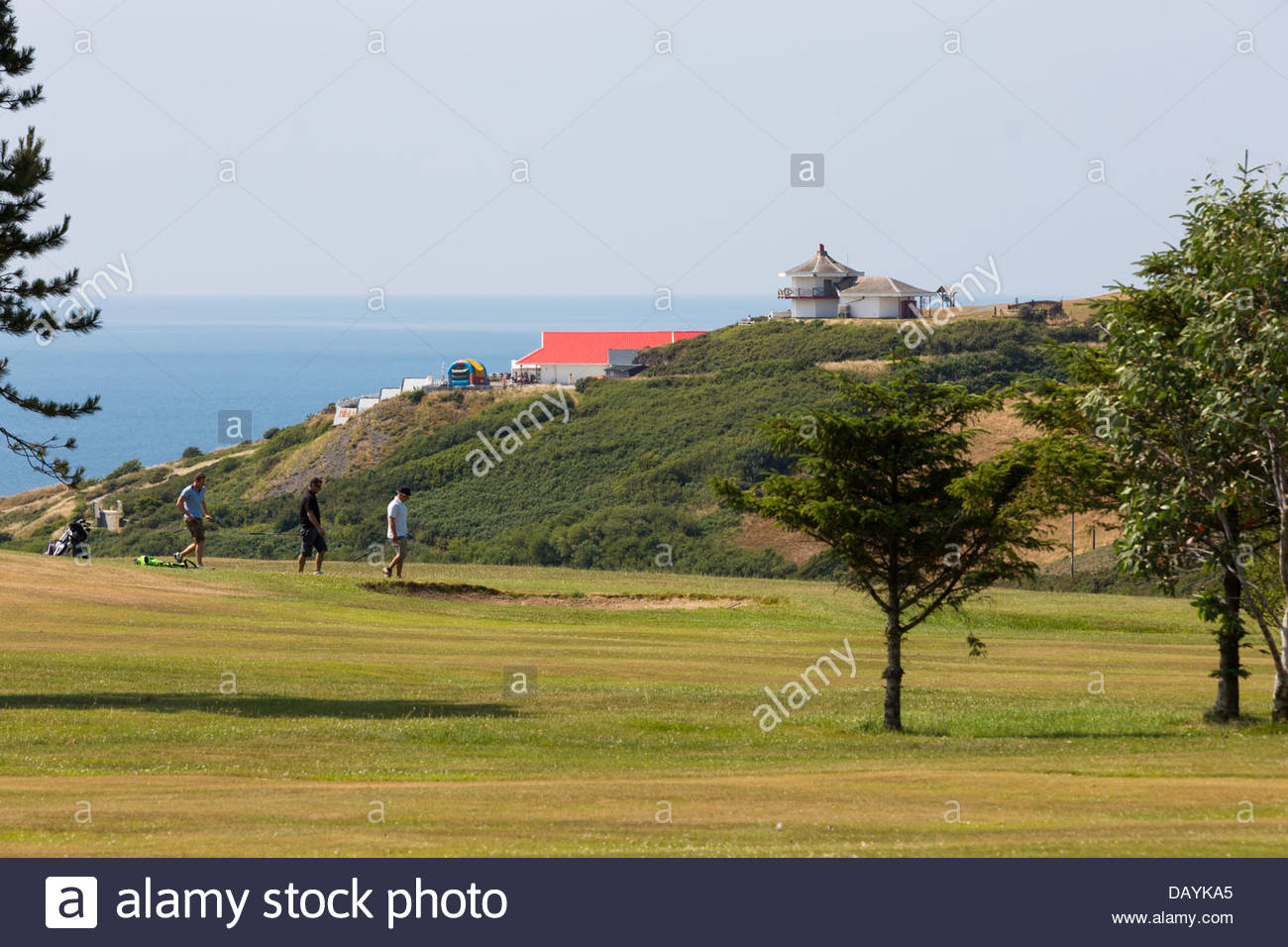 Golfers at Aberystwyth golf course on a bright sunny day with the sea, camera obscura and constitution hill in the - Stock Image