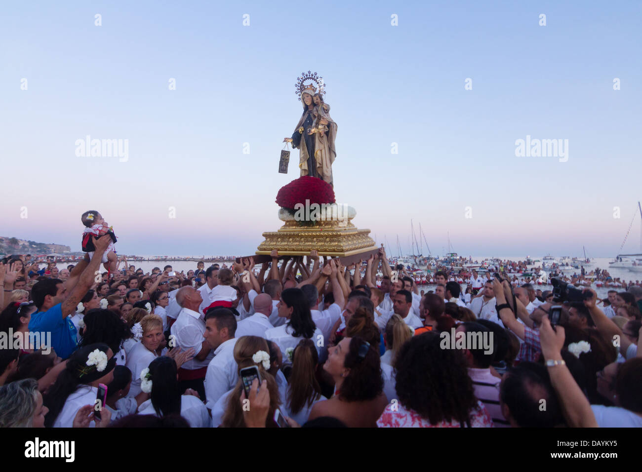 Unidentified local worshiper lift his daughter in front of a religious image at the beach during the Virgen del - Stock Image
