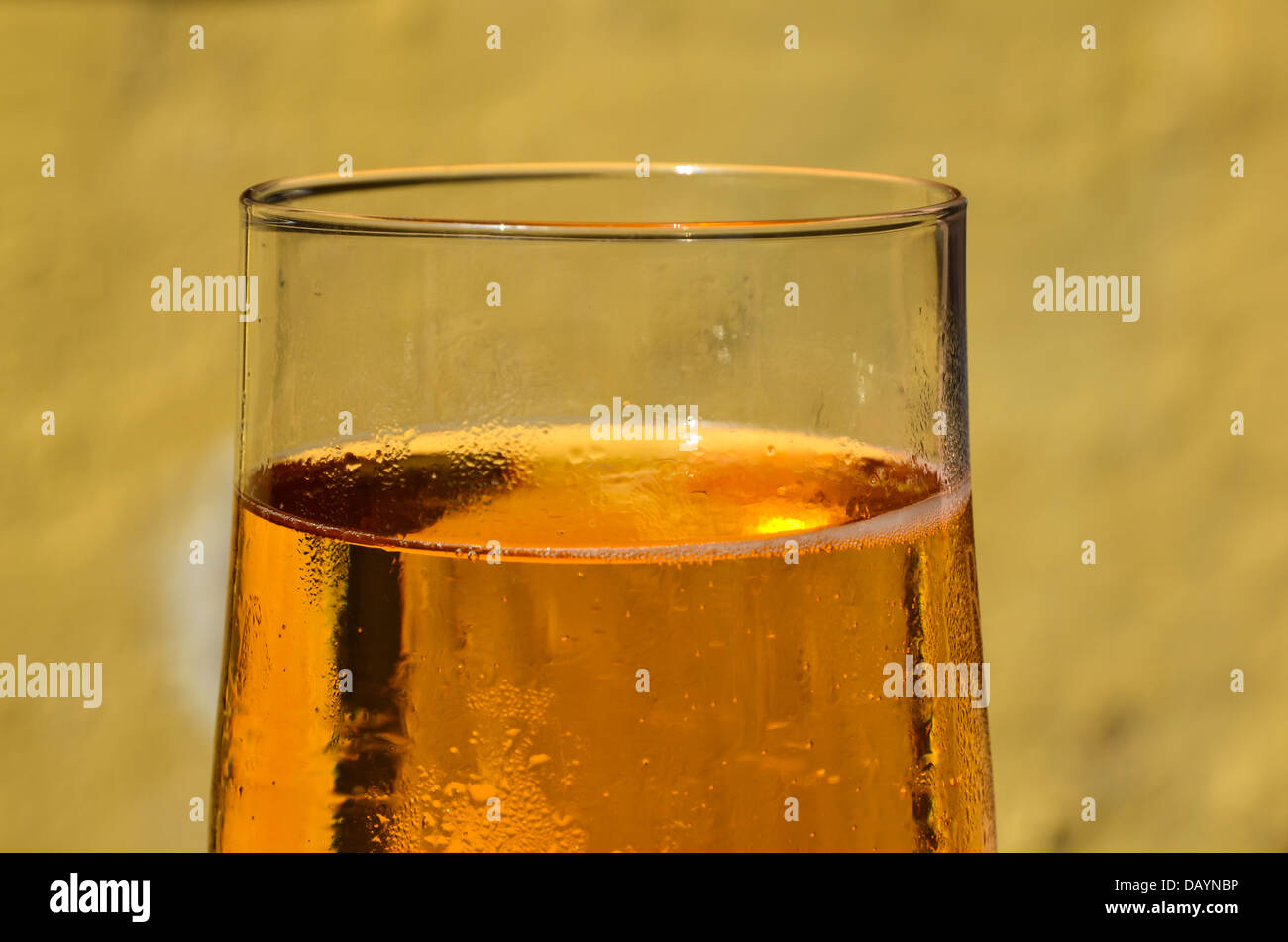 Detail of a cold beer in a glass at soft and yellow background - Stock Image