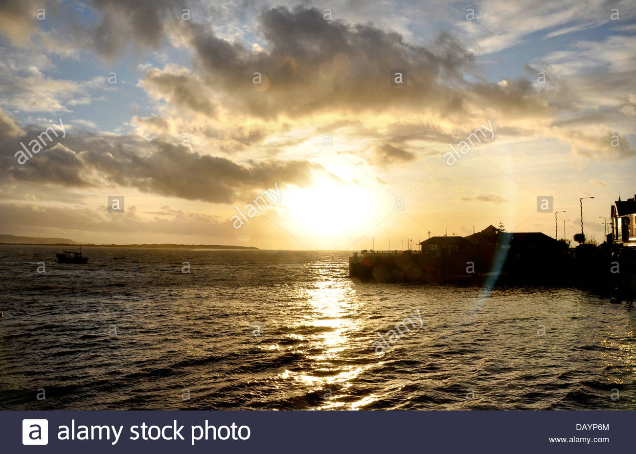 Lens flare as the sun sets at Aberdovey, Gwynedd, Wales - Stock Image