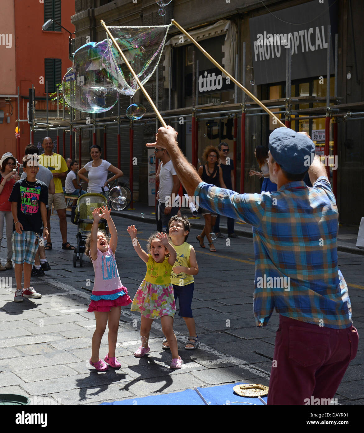 Man making bubbles entertaining children in Bologna Italy - Stock Image