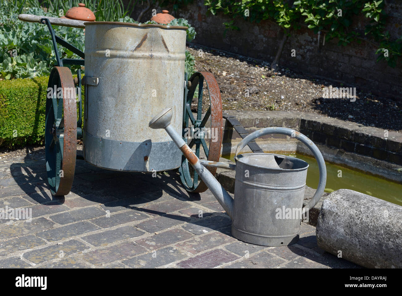 An old galvanized water bower and watering can sitting next to a small water reservoir  in a kitchen garden ( garden - Stock Image