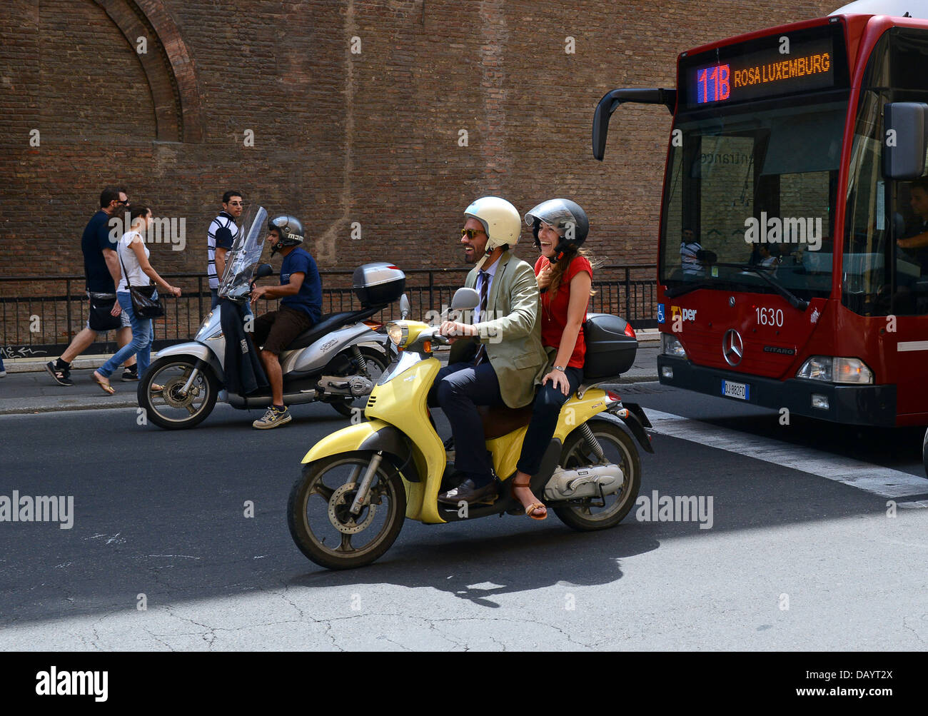 Happy smiling man and woman riding Yamaha scooter in Bologna Italy - Stock Image