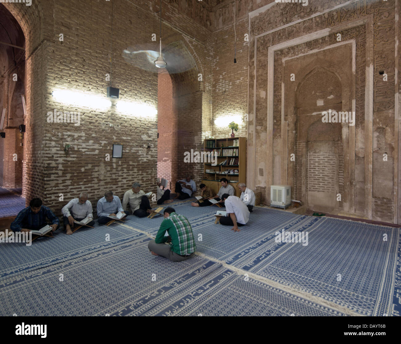 Muslims awaiting the iftar breaking of the fast in Ramadan read the Quran in the ancient mosque in the village of - Stock Image