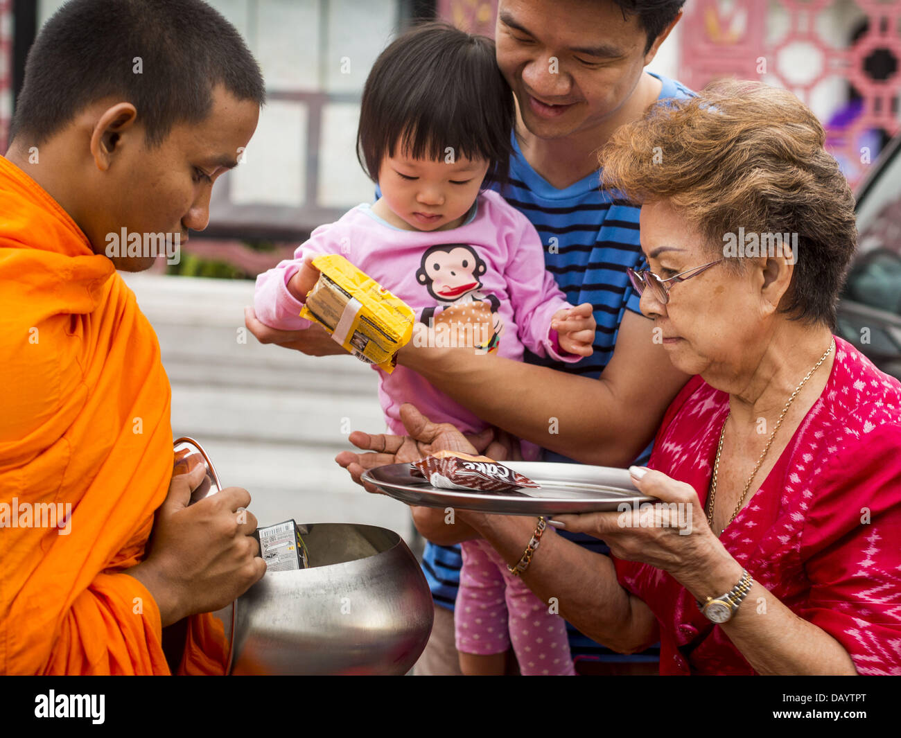 Bangkok, Thailand. 21st July, 2013. Three generations of a family give food to a monk to make merit at Wat Benchamabophit Stock Photo