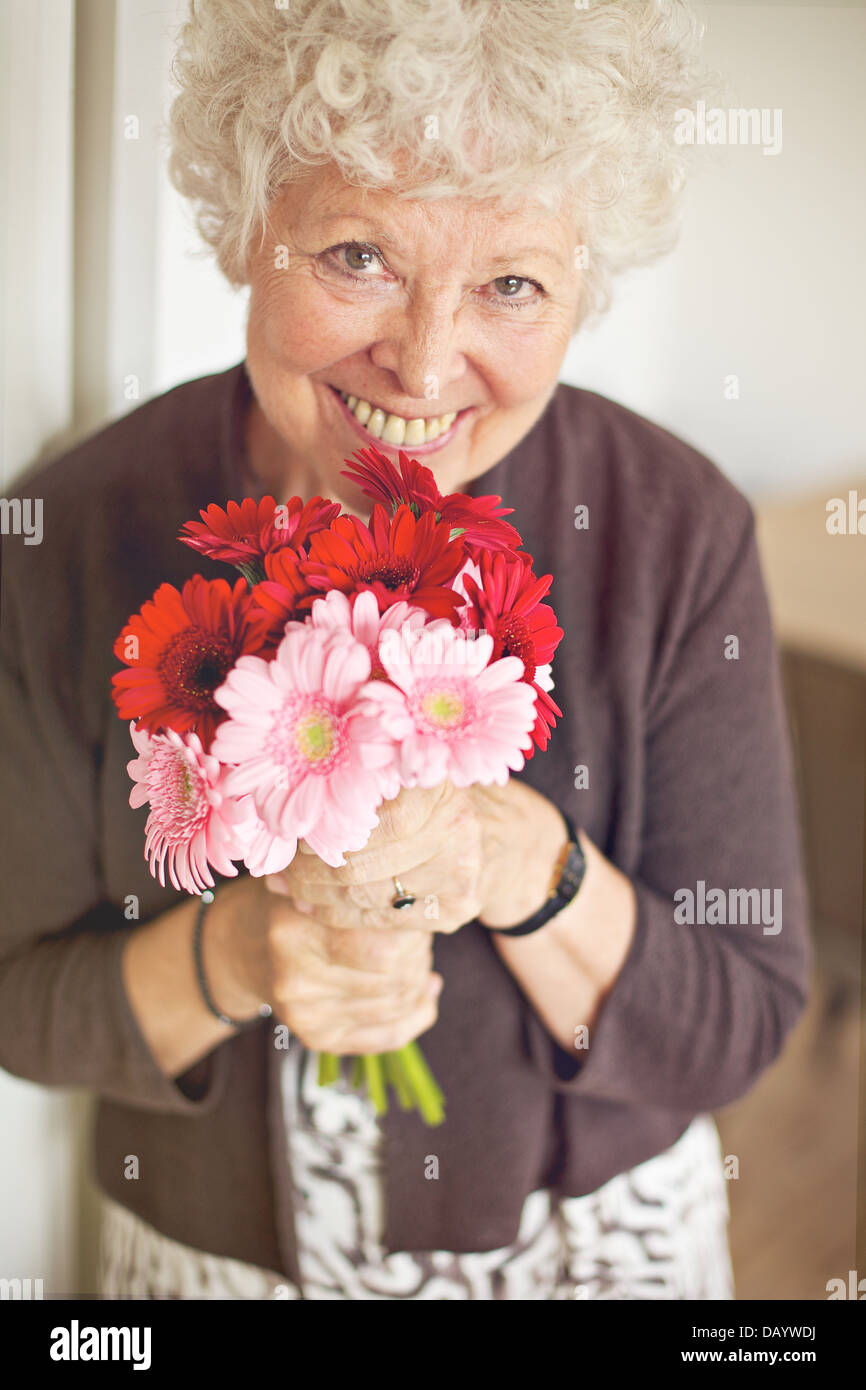 Smiling senior woman holding a bouquet of flowers - Stock Image