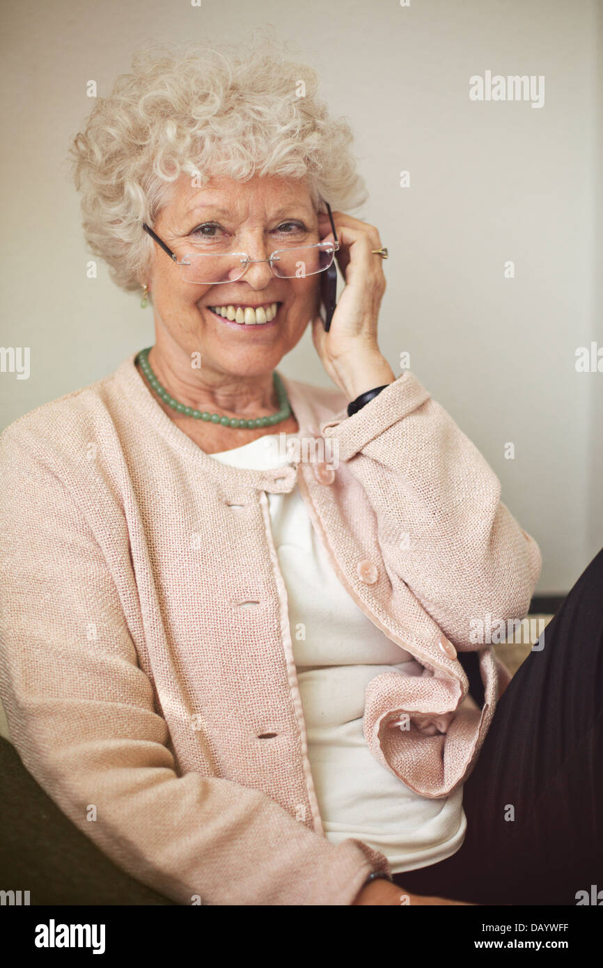 Cheerful woman smiling while calling on her cell phone - Stock Image