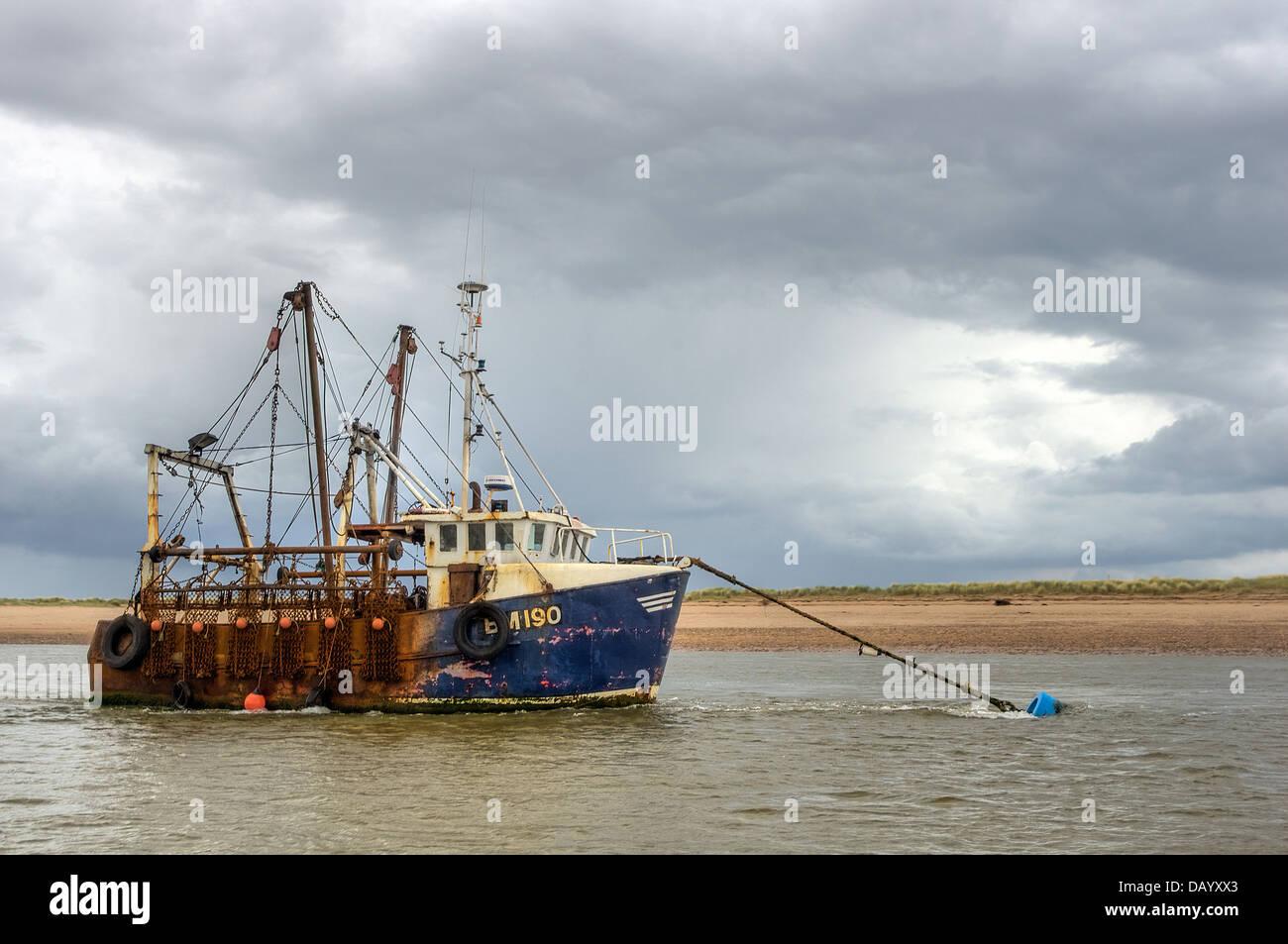 'Marina' (BM190) fishing vessel, alongside the Dawlish Warren sand spit in the Exe Estuary - below a retreating - Stock Image