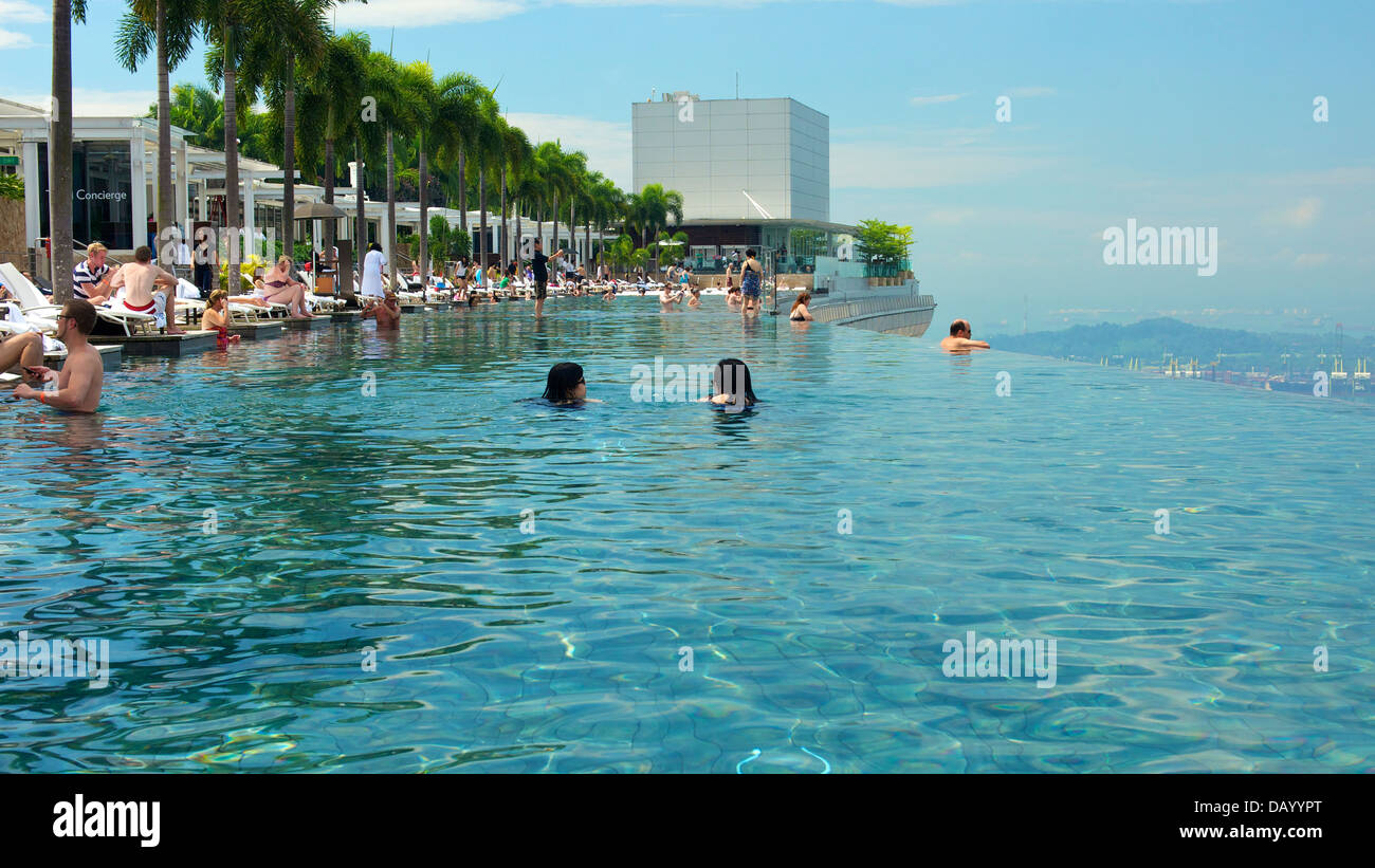 Guests of Marina Bay Sands enjoying a soak at the hotel's rooftop infinity pool and taking in the sights of - Stock Image