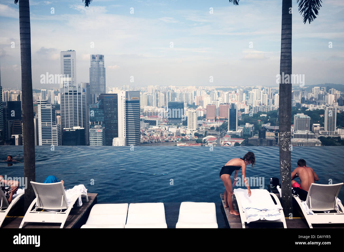 Hotel guests enjoying Singapore's city skyline by the Marina Bay Sand's infinity pool deck - Stock Image