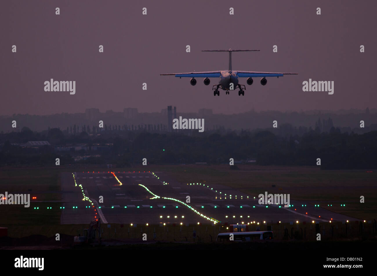 Aircraft Landing At Birmingham Airport With Runway Landing Lights Visible,  UK   Stock Image