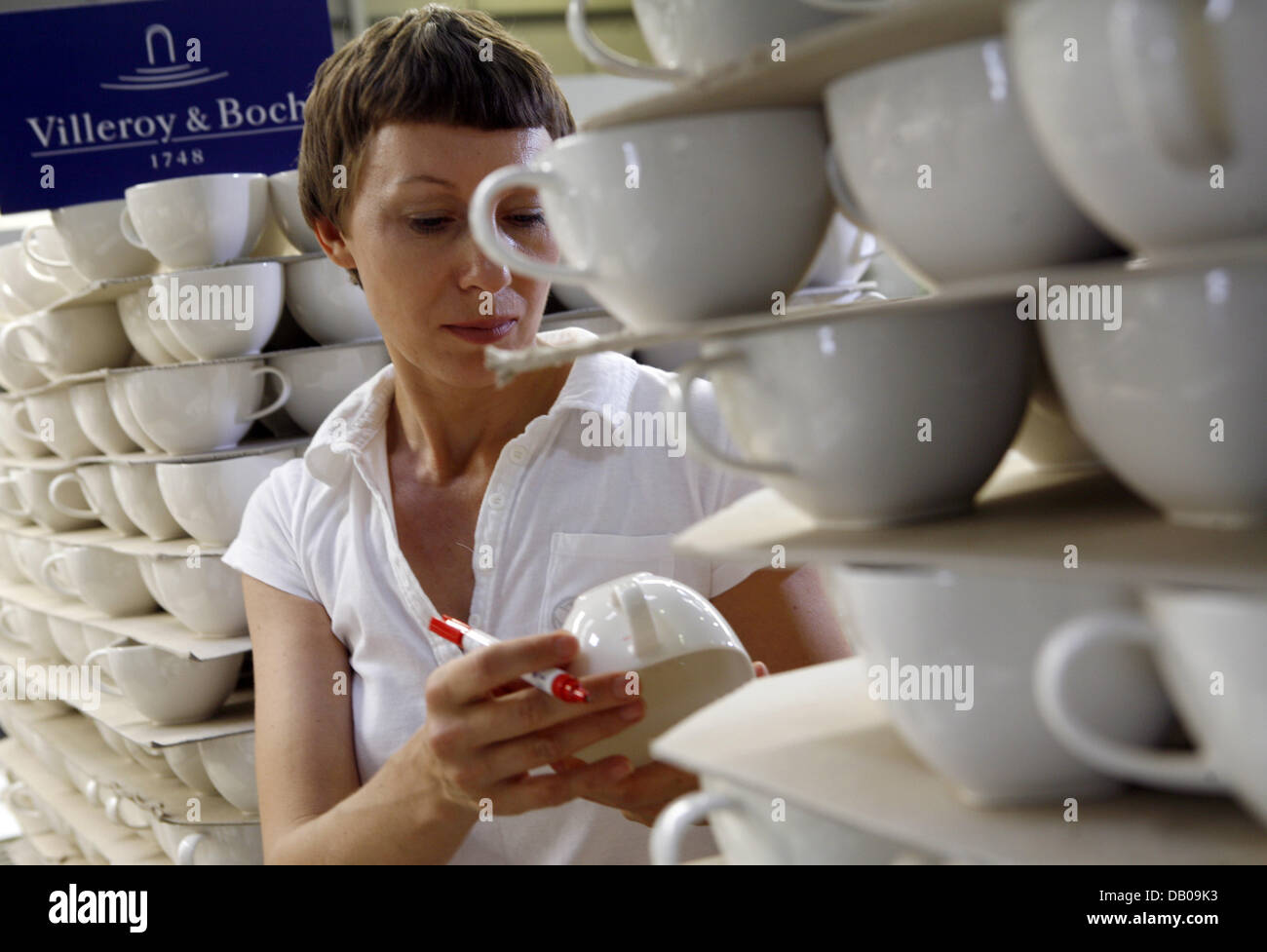 A worker checks cups at the tableware manufacturer Villeroy