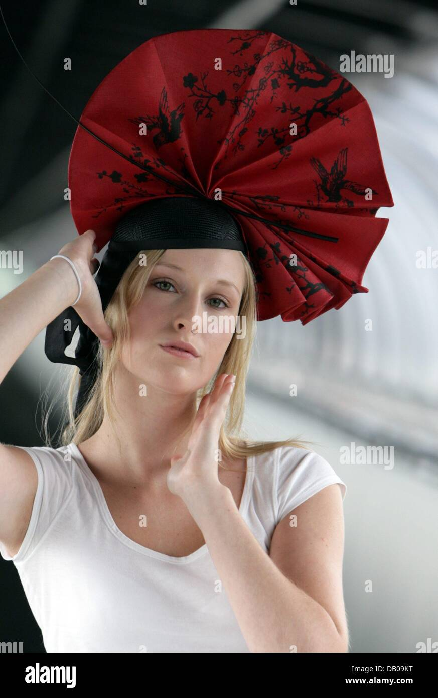 Model Juliane poses with the hat creation 'Sunset Glow' by Svenja Otten of 'Hutsalon Schmedes' at - Stock Image