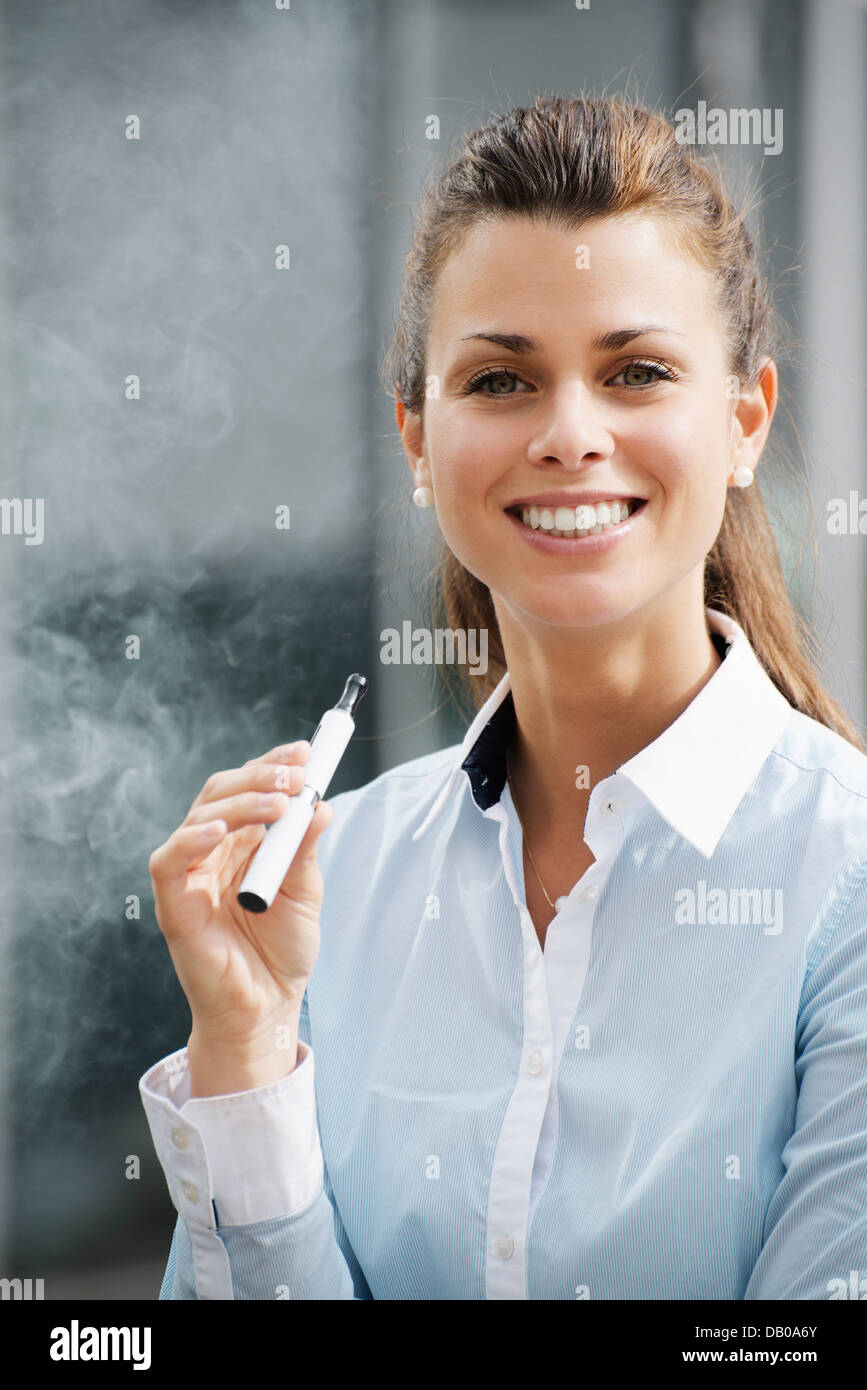 portrait of young female smoker smoking e-cigarette outdoor office building and looking at camera - Stock Image