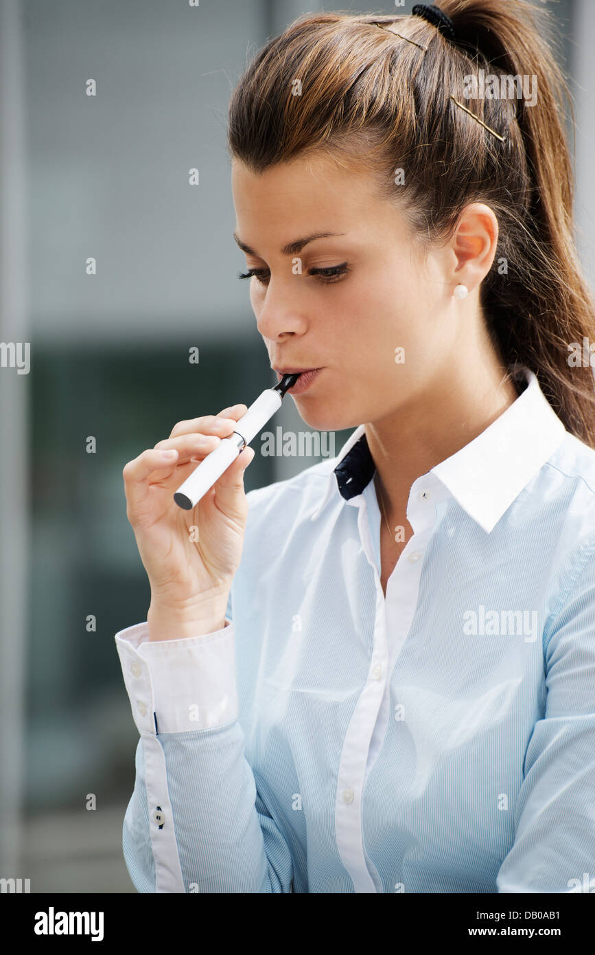young female smoker smoking e-cigarette outdoors. Head and shoulders, side view - Stock Image