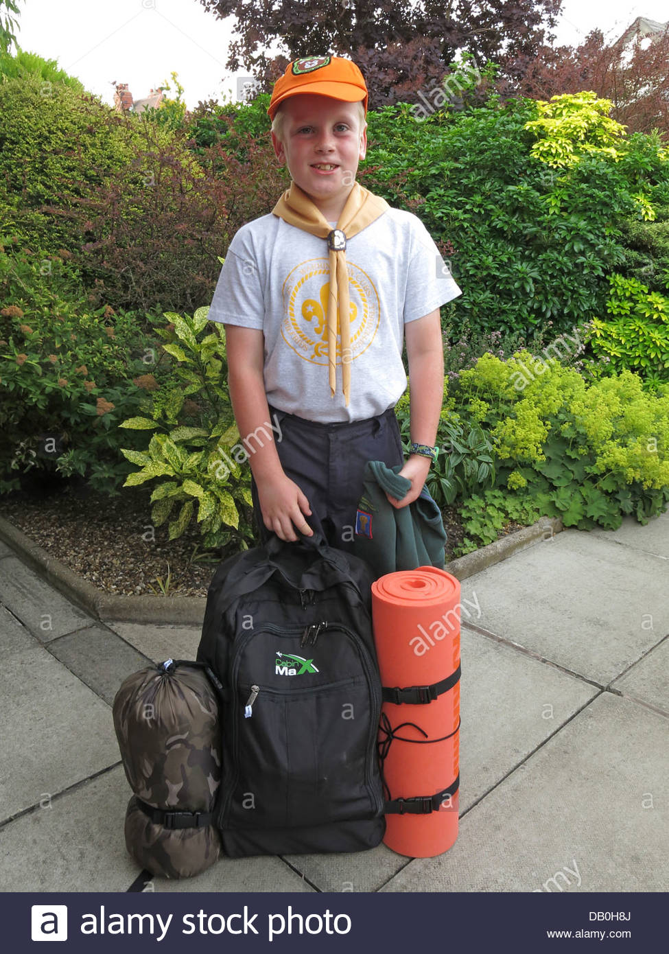 Cub Scout smiling and ready for scout camp overnight one summer weekend - Stock Image