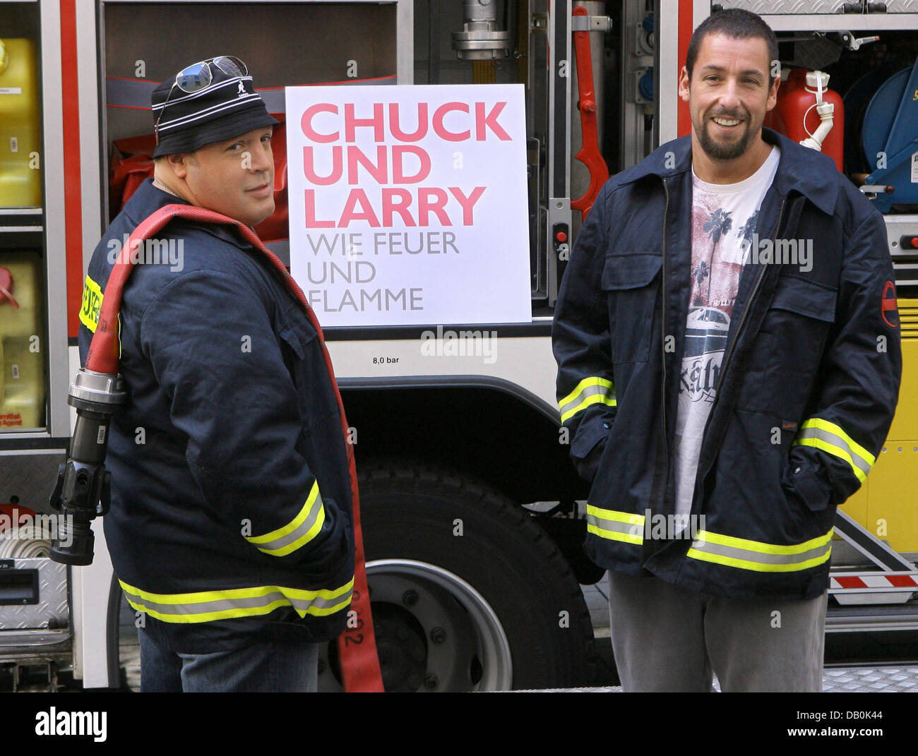 Actors Kevin James (L) and Adam Sandler pose in front of a fire