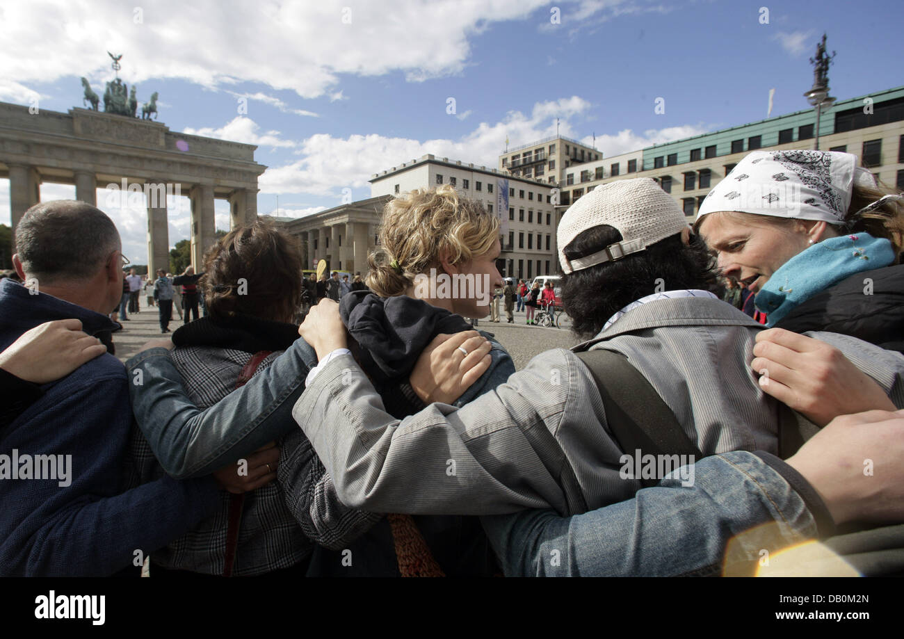 Total strangers hug during the performance 'The utopia of a 20-minutes-hug' at Brandenburg Gate of Berlin, - Stock Image