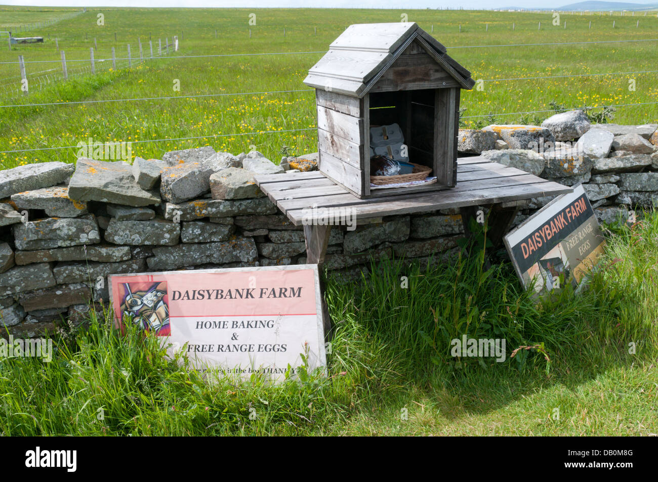 Farm produce for sale beside a footpath with an honesty box for payment. Stock Photo
