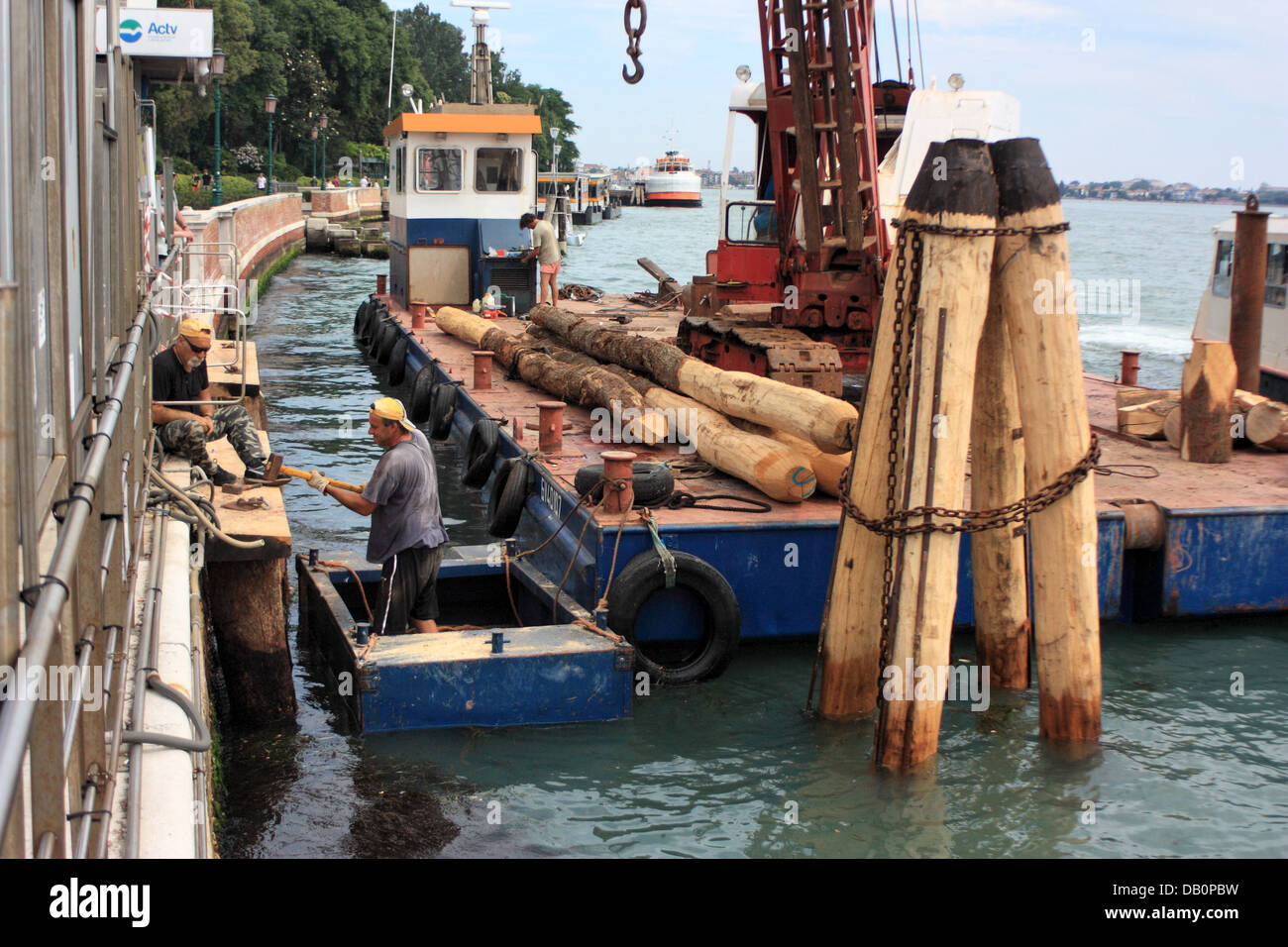 Construction work - rebuilding the wooden mooring poles of a Vaporetto stop. - Stock Image
