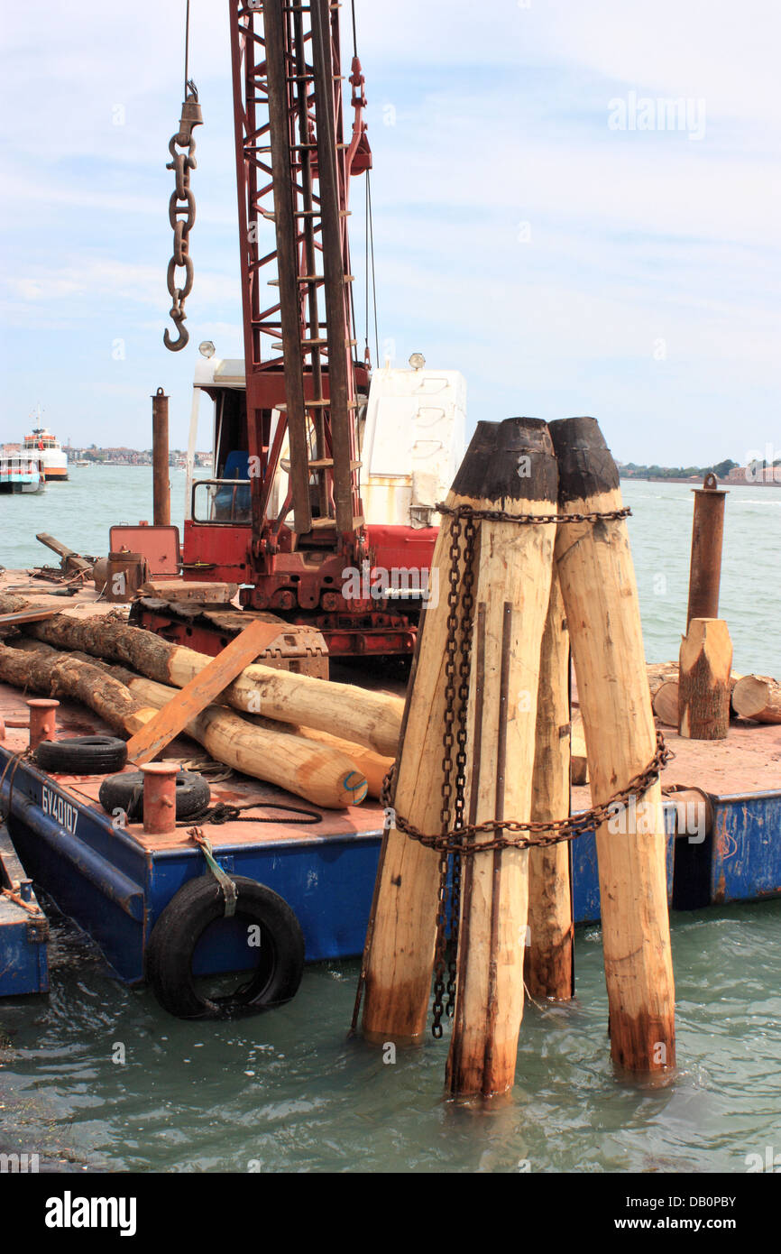 Construction work - rebuilding the wooden mooring posts of a Vaporetto stop. - Stock Image