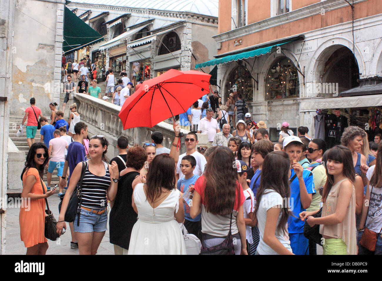 Happy young people on a guided tour in Venice (in front of Rialto Bridge). Stock Photo