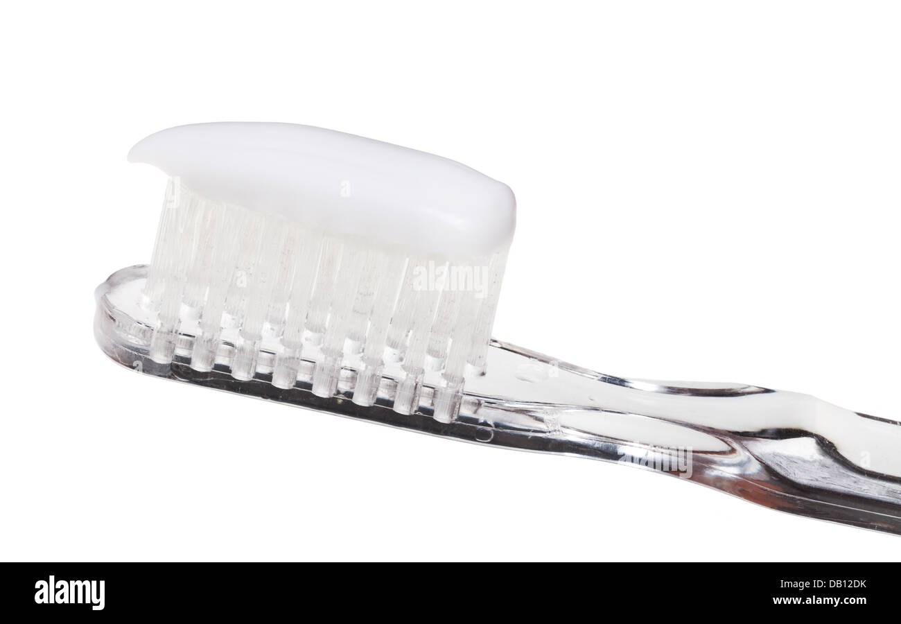 extruded toothpaste on toothbrush close up isolated on white background - Stock Image