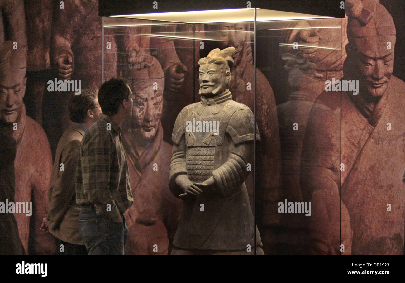 Visitors observe a Terracotta Army's soldier of the exhibition 'Power and Death - China's first Emperor - Stock Image