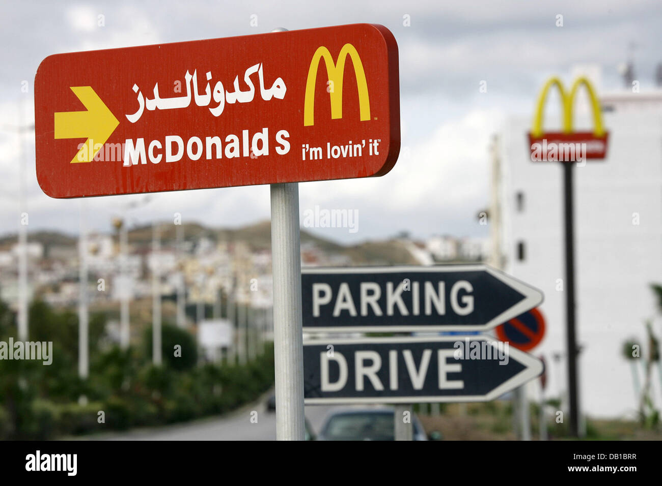 A sign indicates the way to a restaurant of the fastfood chain McDonald's in Arabic and Latin letters in Tetouan, - Stock Image