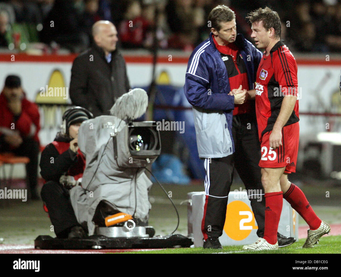 Bernd Schneider (R) of Leverkusen is cheered and substituted by his head coach Michael Skibbe (C) during the UEFA Stock Photo