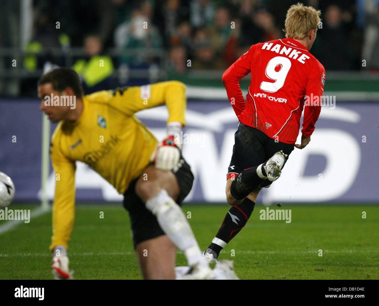 Mike Hanke of Hanover (R) scores the 4-3 against goalkeeper Tim Wiese of Bremen during the Bundesliga match Hanover Stock Photo