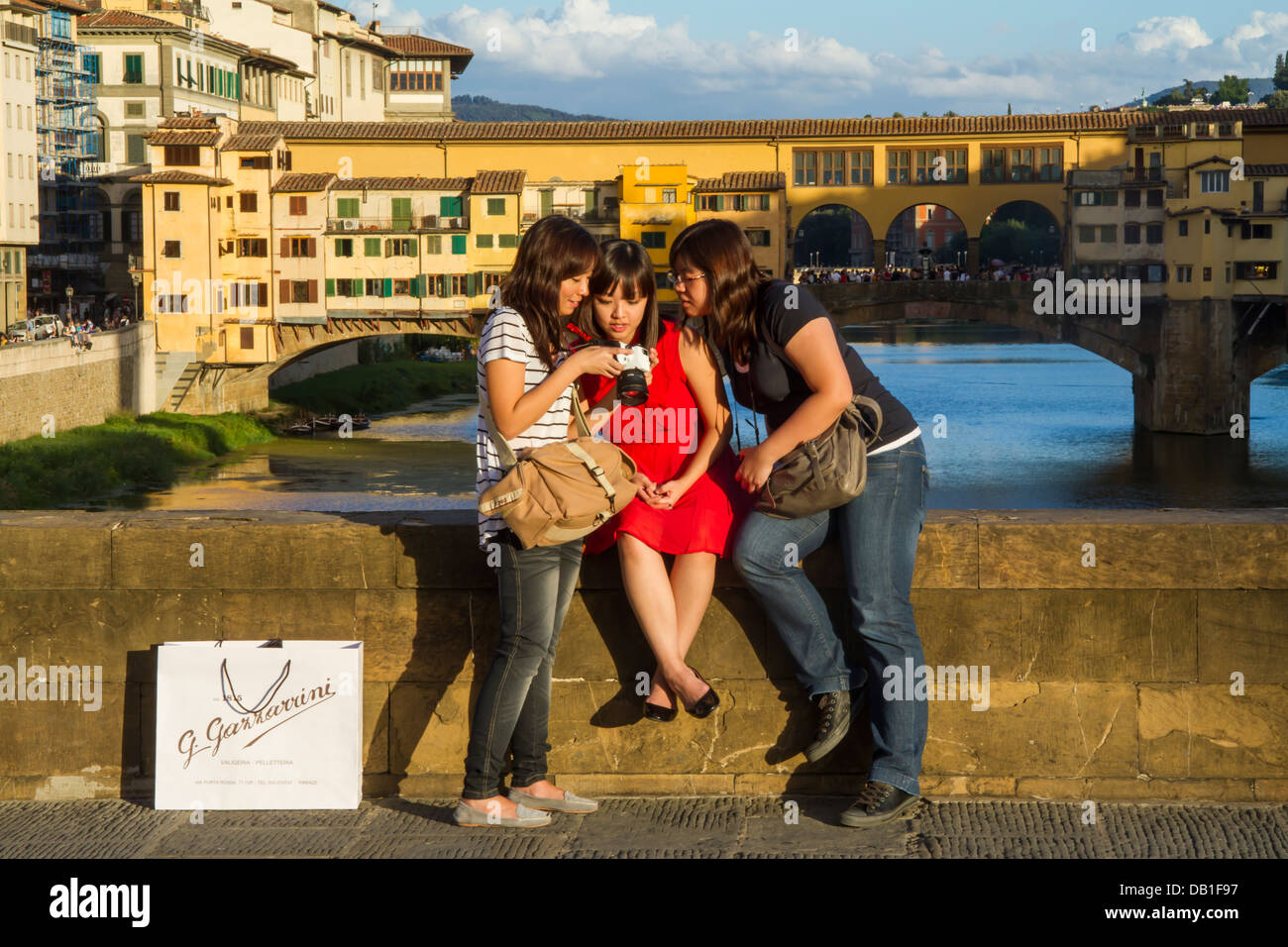 Three tourist girls looking at photos on their camera with ...