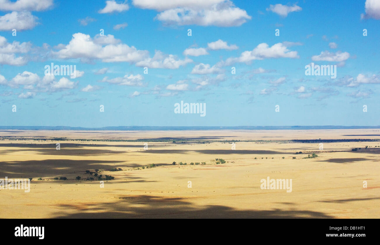 Dry grasslands and a blue sky with clouds in a remote part of outback Queensland, Australia - Stock Image