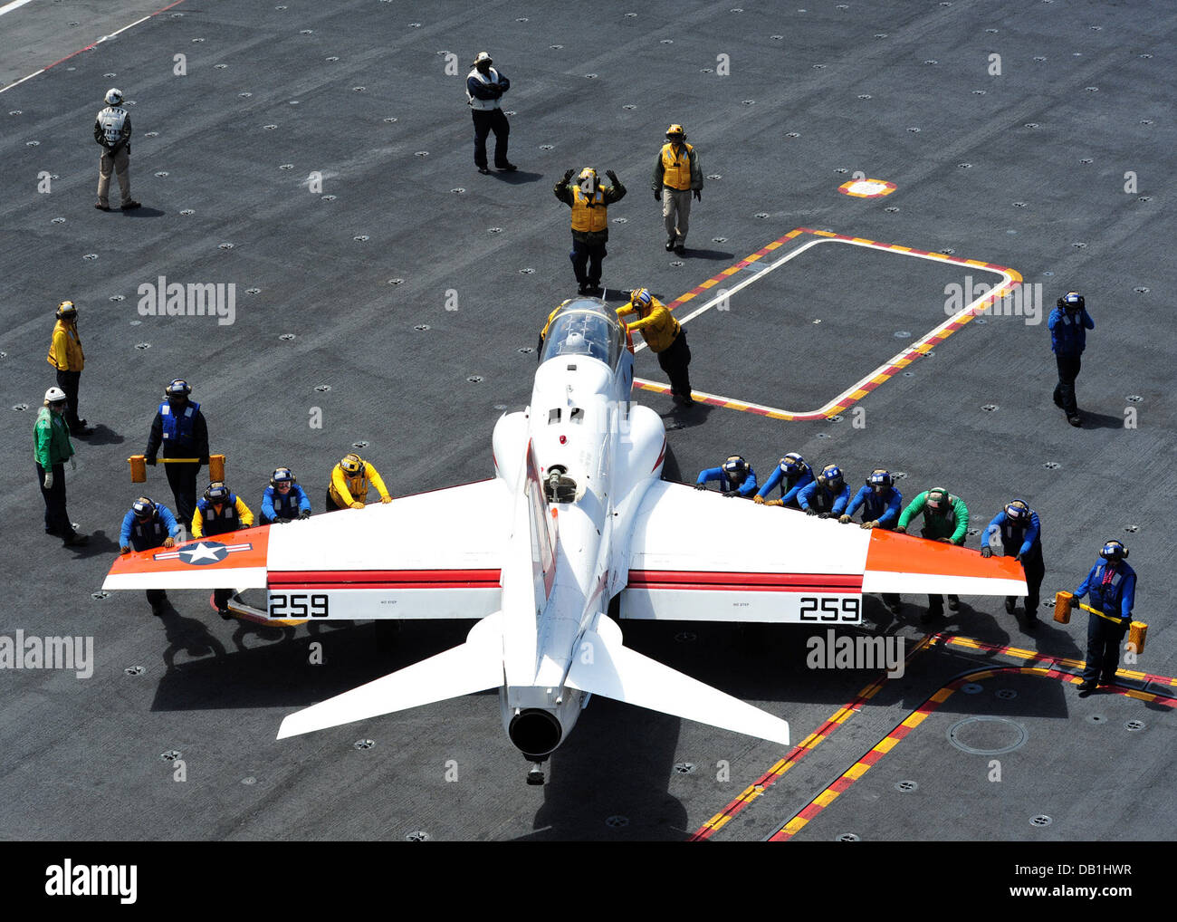 Sailors push a T-45C Goshawk training aircraft from the Redhawks of Training Wing 2 into a maneuvering position - Stock Image