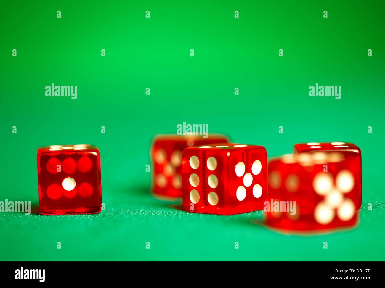 red dices on green cloth... - Stock Image