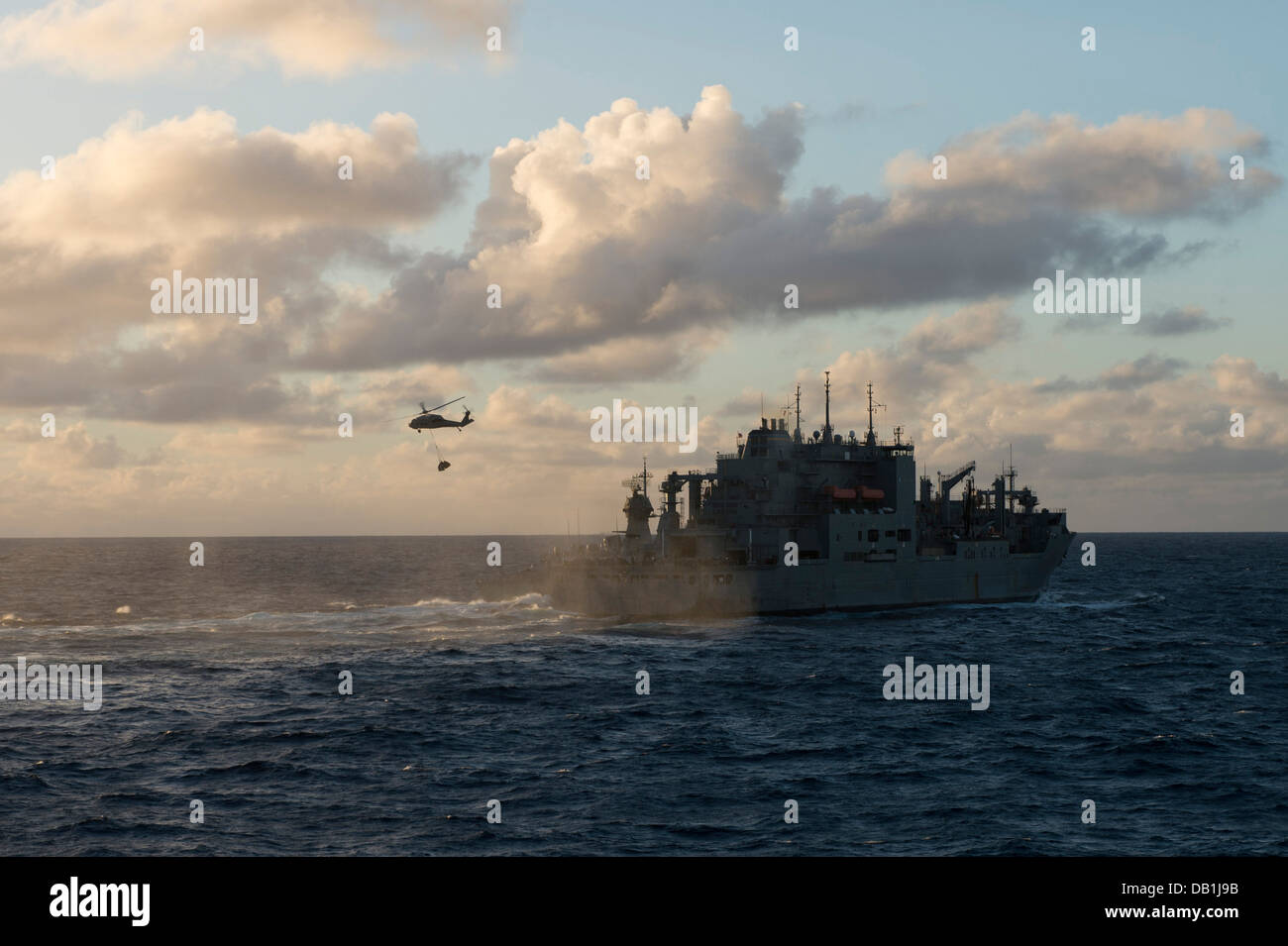 "An MH-60S Seahawk helicopter from the ""Island Knights"" of Helicopter Combat Support Squadron (HSC) 25 carries supplies - Stock Image"