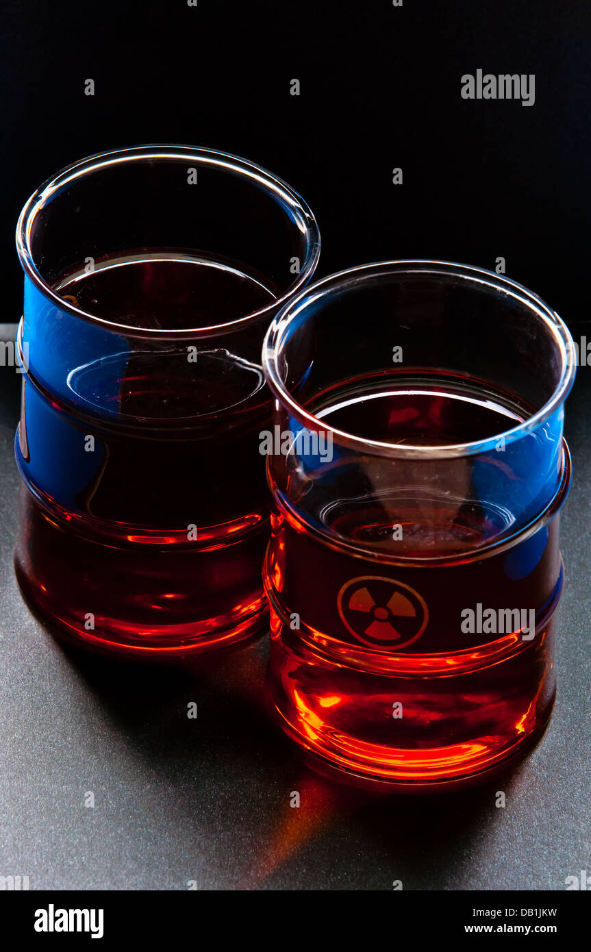 Two transparent glasses and tea with atomic sign - Stock Image
